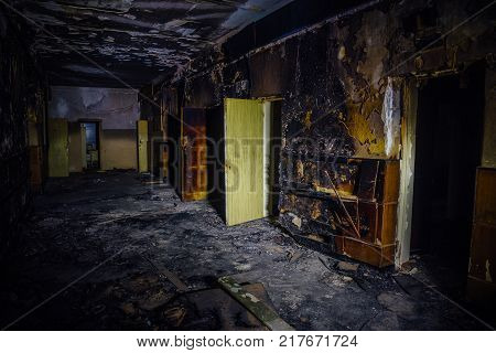 Burned by fire interior of old hospital. Charred walls and doors of corridor.