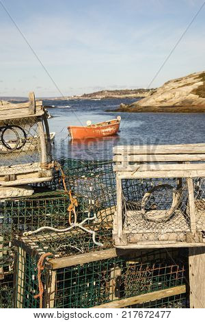 Wooden Lobster Traps On Dock In Peggys Cove, Nova Scotia, Canada With Boat