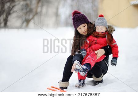 Young asian woman helping caucasian toddler boy with his winter clothing. Babysitting/childcarer concept.