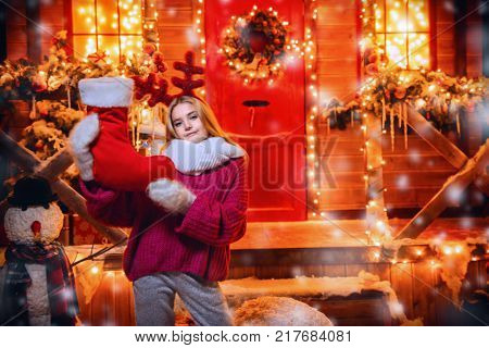 Pretty child girl is standing near her house decorated for Christmas with reindeer antlers on the head and holding a christmas sock. Merry Christmas and Happy New Year.