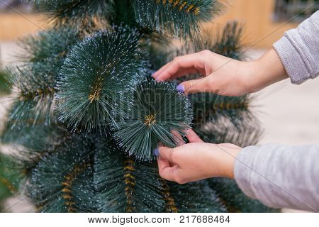 closeup view of hands choosing faux Christmas tree on Christmas Eve. Save nature concept
