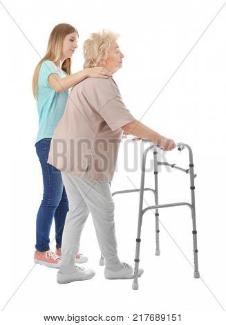 Young woman and her elderly grandmother with walking frame on white background