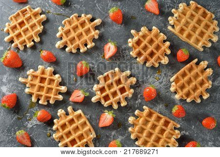 Traditional waffles with maple syrup and strawberries on a gray background