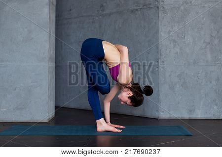 Flexible young woman performing one-leg balance exercise doing half bound lotus standing forward fold pose indoors.