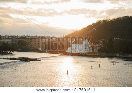 Beautiful view from Charles Bridge. View from the Charles Bridge in Prague at sunset - old architecture, hill with trees, river and birds against sky