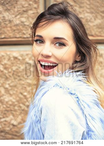 Attractive smiling woman in faux fur vest against brick wall