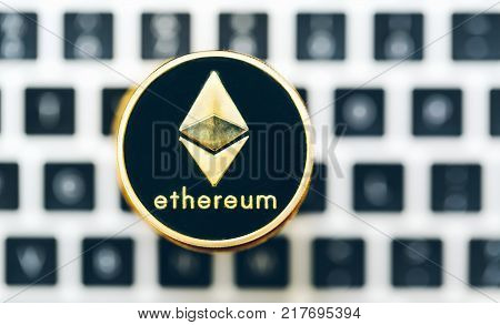 Stack of ethereum ether coins with a laptop in the background