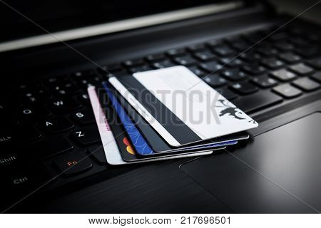 Credit cards on a laptop. Several credit and discount cards are on the keyboard of a black laptop. Online payment. Cashless settlement. Buying goods via the Internet. transfer of money.