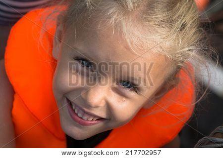 Happy girl with life jacket enjoying in sea.