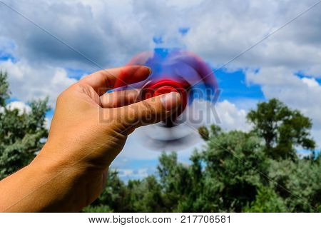 Red fidget spinner rotates in a female hand
