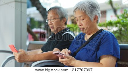 Retired couple use of mobile phone at street