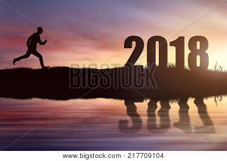 Silhouette of businessman running reaching goal of 2018 at sunset background. Happy New Year 2018