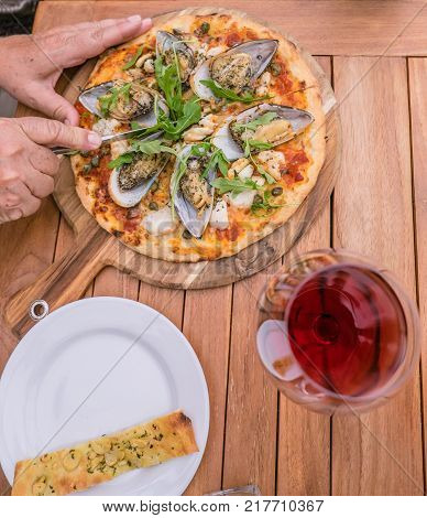 Hands cutting a seafood pizza with New Zealand NZ green lipped mussels calamari squid capers and rocket - with glass or red or rose wine and garlic bread. Viewed from above. Wooden timber table and board.