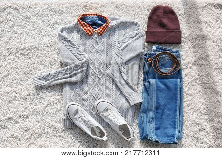 Set of stylish female clothes and accessories on fluffy carpet