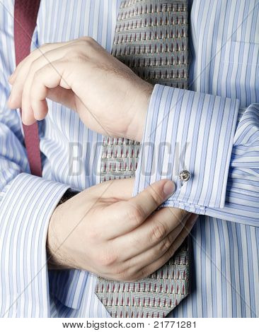 Businessman fastening cufflinks