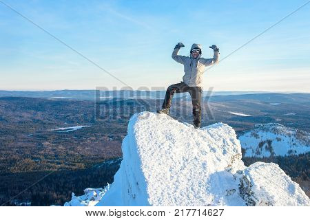 The mountaineer climbed the mountain top covered with ice and snow, man hiker standing at the peak of rock and celebrates the success. Winter season