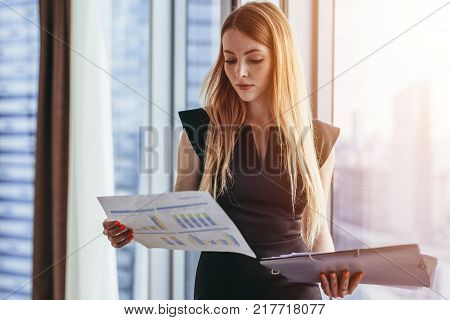 Female financial analyst holding papers studying documents standing against window with city view.