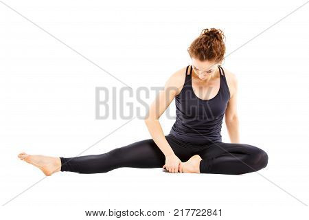Young fit woman doing pilates excercises isolated on white background. Slim girl stretching on the floor