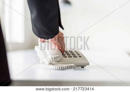 Businessman holding a telephone receiver as if about to place it on base or just has picked it up.