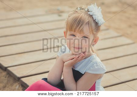 Young Cute Baby Girl Enjoying Childhood Summer Time On Sandy Beach Posing On Wooden Pier Bridge Wear
