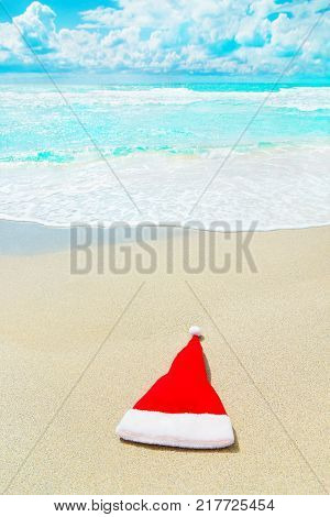 Red Santa Claus hat on white sand of tropical beach against waves - Merry Christmas or Happy New Year's vacation concept vertical background