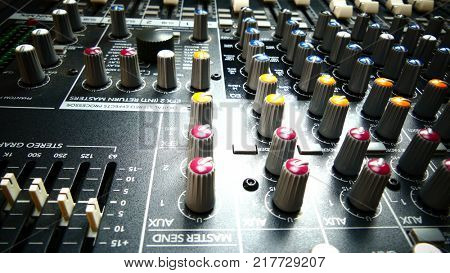 Audio mixer buttons and knobs. Music production and sound engineering background.