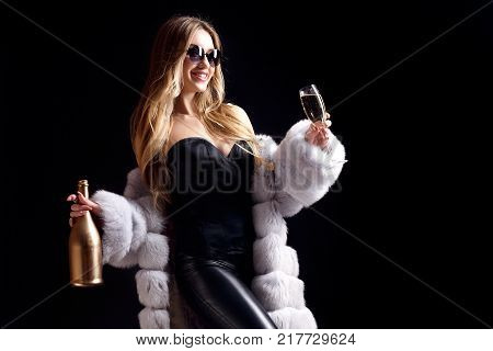 Well-dressed pretty woman in sunglasses drinking champagne and standing on black background.