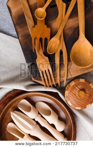 A top view on wooden cutlery spoon, fork, plate, bowl, knife on a light marble background. Cutlery for cooking. Close-up of objects.