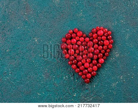 Red bilberry or cranberry in heart shape on green cement background. cowberry heap in heart form top view. Copy space for text.