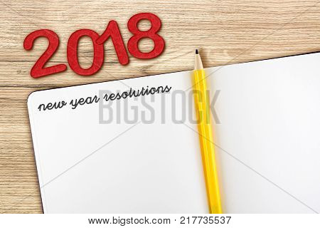 Top view of 2018 new year resolution with blank open notebook and yellow pencil on wooden table topMock up for adding your content or design
