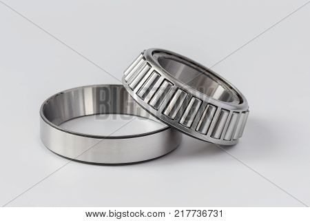 Tapered roller bearing on a light background. Clip and rollers in the separator separately poster