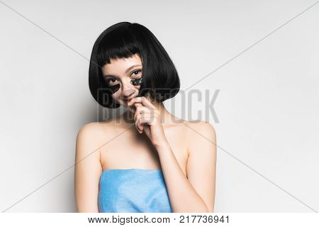 beautiful young girl with short black hair, in a blue towel, under the eyes of black silicone patches