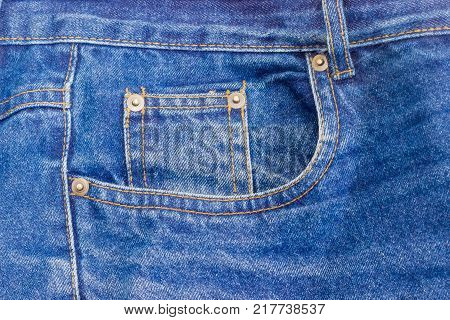 Fragment of the top of the old classical blue jeans with waistband belt loop reinforcing by copper rivets pocket and little pocket