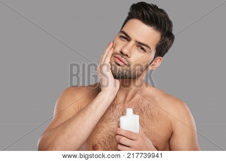 Used to look perfect. Handsome young man applying aftershave lotion and smiling while standing against grey background