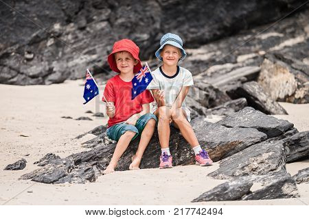 Boy and girl sitting on the rock with Australian flags on Australia day