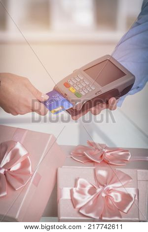 Wireless payment terminal with credit or debit card at shop with gifts in the background