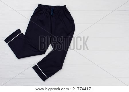 Pajama pants for teenager boy on shop display. Dark blue and white. Smooth and soft cotton, waistband with drawstring.