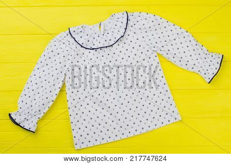 White blouse with sailor pattern. Anhcors and handwheels, ruffle cuffs and collar. Girls' top on yellow wooden table.