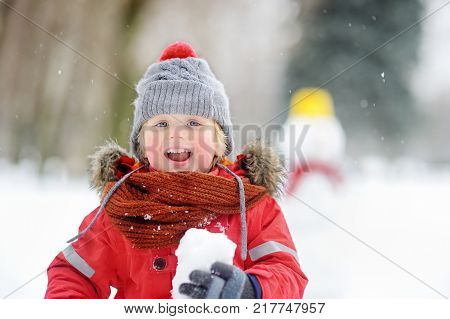 Little boy playing with snowballs with snowman on background. Active outdoors leisure with children in winter. Kid during stroll in a snowy winter park. Snowball fight