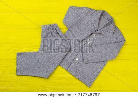 Boys pajama set on yellow table. Simple design and gray melange fabric. Comfy pants and shirt for good sleep.