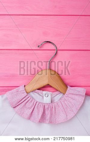 Kids garment on wooden hanger, close up. Cute ruffle collar on girls' blouse. Pink wooden background.