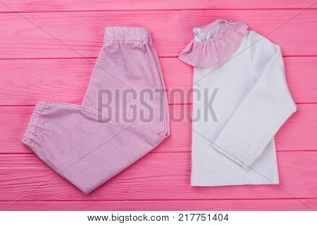 Pink and white pajama set on wooden background. T-shirt with ruffle collar and pants. Snug and soft sleepwear for toddler girls.