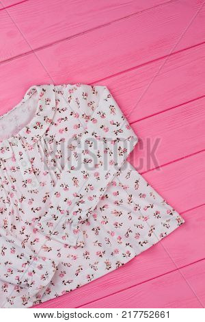 Girls' top with ruffle collar. Cotton fabric with floral pattern, button-up neck. Kids clothing store.