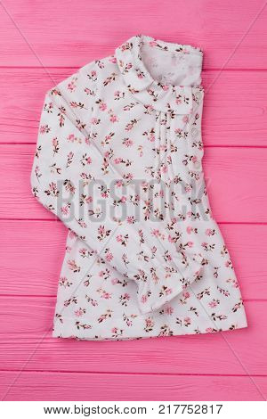 White tunic with floral pattern. Rounded ruffle collar and long sleeves. Pink wooden display at the store.