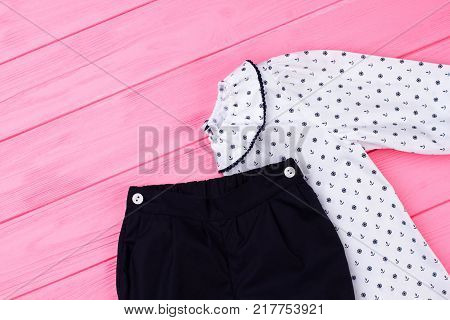 Girls pajama set on pink. Top with ruffle collar and pants. Clothes on wooden rack at the store.
