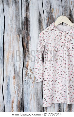 Floral nightgown for young girls on wooden background. Long sleeve and ruffle collar. Sleeping garment on wooden hanger.