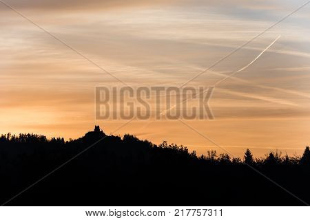 Contrail in colorful morning sky with forested mountain silhouette with a castle building Grad Smlednik near Vodice Slovenia.