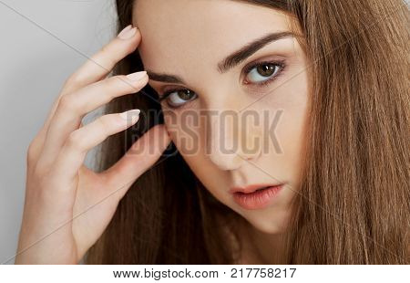 Portrait of young woman touching her head, headache concepion.