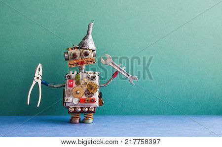 Robotic handyman pliers handwrench. Fixing maintenance concept. Creative design toy with metal funnel hopper, cogs wheels gears silver metallic body. Green wall, blue floor background. Copy space photography.