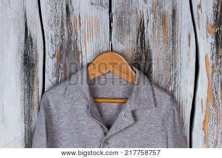Close up on gray melange shirt on hanger. Soft cotton garment for comfortable rest at night. Boys clothing line.